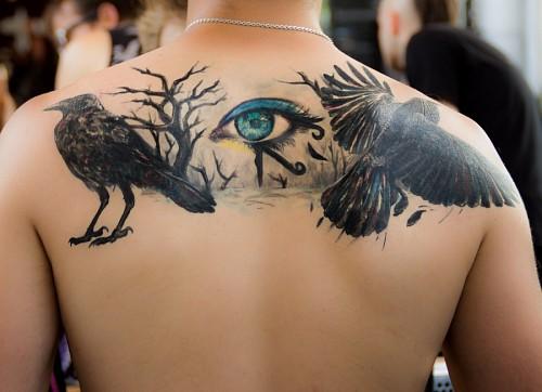 Tatuaje de ojo de horus en espalda masculina