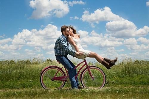 Feliz pareja de jóvenes en bicicleta