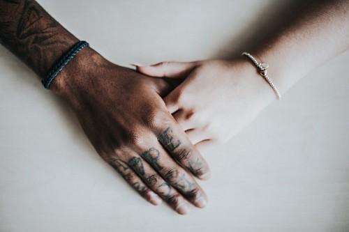 Pareja de la mano con tatuajes