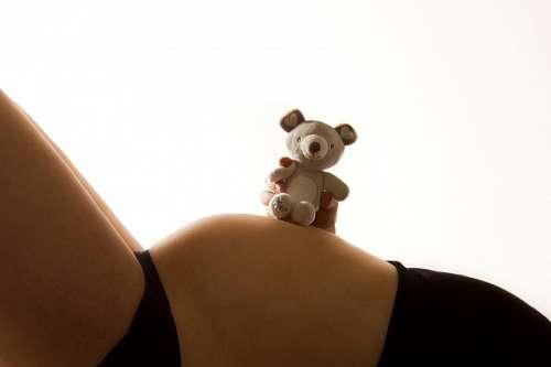 Mujer embarazada con oso de peluche