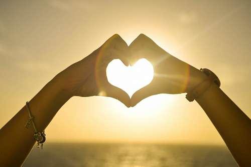 Mujer formando corazon iluminado por el sol