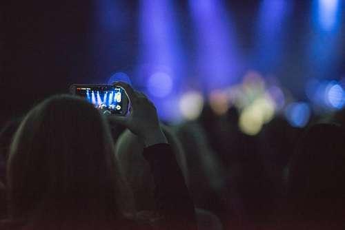 Una mujer con celular en Concierto