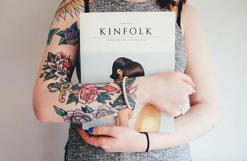 Chica con los brazos tatuados sosteniendo libro