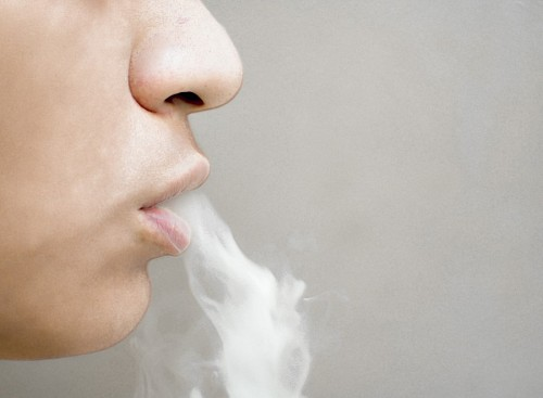 Mujer vapeando con cigarrillo electronico