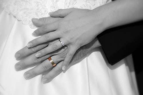 Manos de recien casados con sus flamantes alianzas