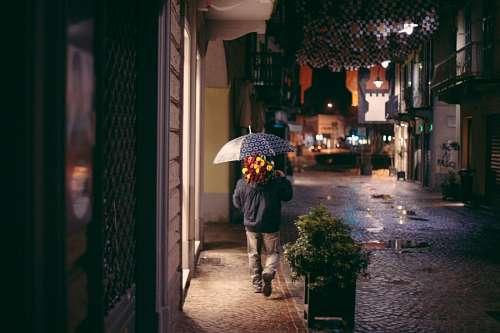 Pretendiente bajo la lluvia con ramo de flores