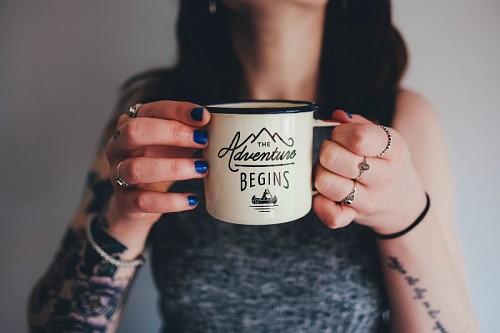 Joven chica tatuada sosteniendo una taza