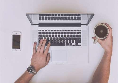 Hombre con laptop tomando cafe