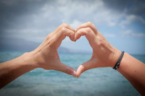 Manos de hombre formando un  corazón en la playa