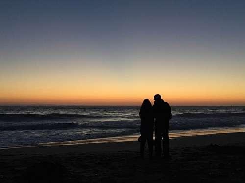 Enamorados en atardecer junto al mar