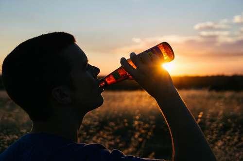 Hombre tomando un refresco al atardecer