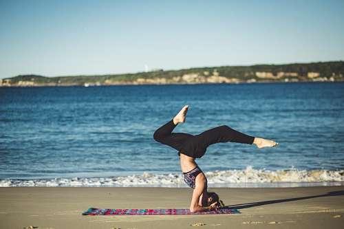 Mujer practicando Yoga en la playa