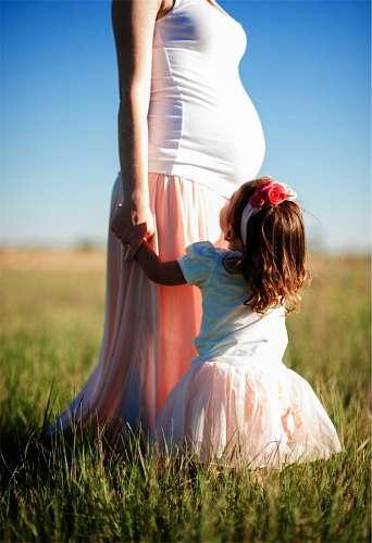 Madre embarazada con su hija en exterior