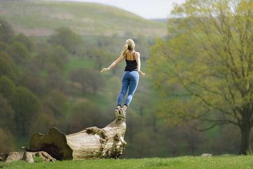 Mujer haciendo equilibrio sobre un tronco