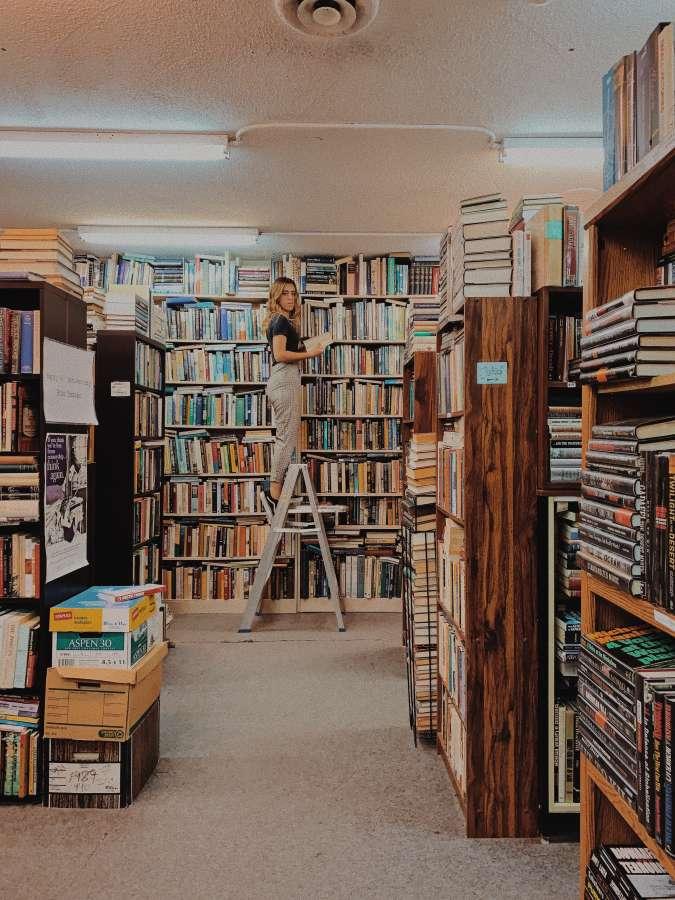 Imagen de mujer acomodando libros en el fondo de la