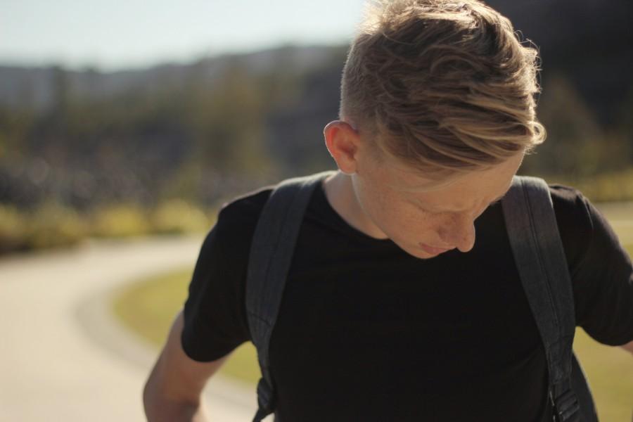 hombre, joven, 15 años, 20 años, rubio, primer plano, mirando hacia abajo, exterior, tristeza, melancolia, viajar, camino, ruta, mochilero, cansancio,