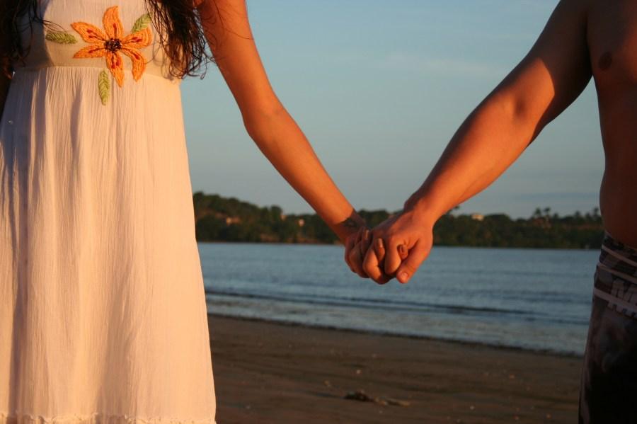 pareja, amor, exterior, playa, tomados de la mano, hombre, mujer, vista de atras, dia, verano, vacaciones, vestido, flor, alegria, felicidad,