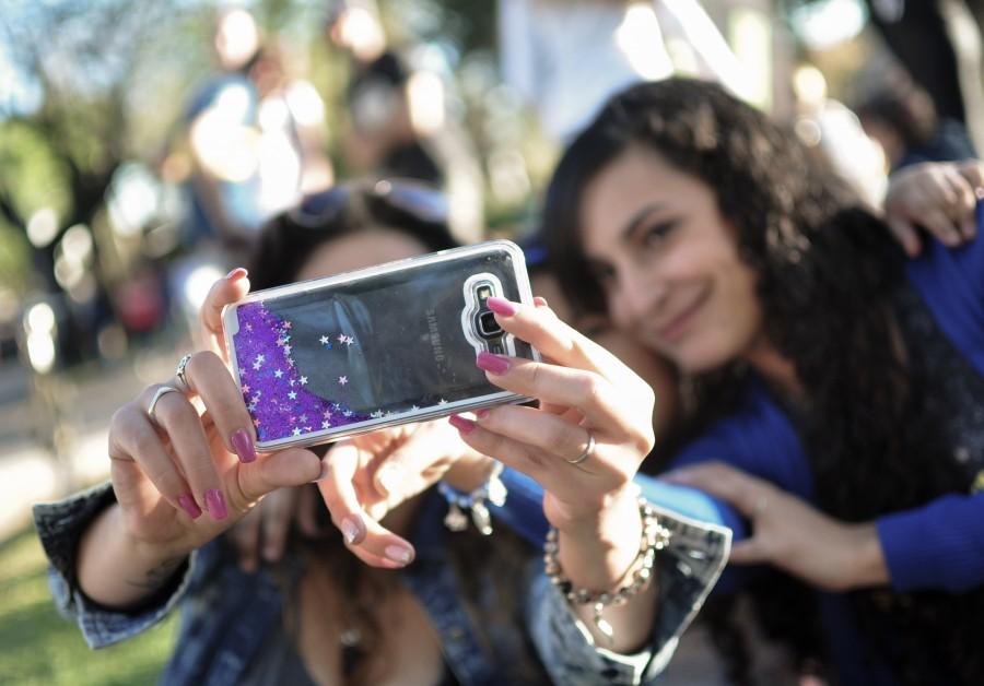 mujeres, jóvenes, 20-25 años, amigas, compañeras, risas, felicidad, aire libre, celular, smartphone, móvil, tecnología, camara, foto, selfie, grupal, brillos, manos. mano, uñas, femenino, violeta, desenfoque, grupo de personas, fotografía