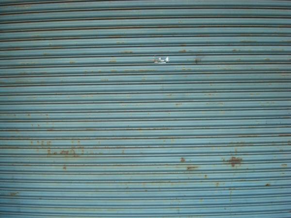 cortina,puerta,metal,metalico,metalica,pliegue,pliegues,rollo,rollos,vista de frente,nadie,fondo,background,primer plano,celeste,oxido,viejo,,prod05